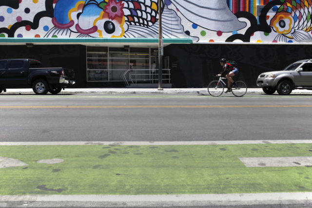 A woman rides her bike down Sixth St. on June 16, 2015, in Las Vegas. Green bike lanes are often more noticeable than others. (James Tensuan/Las Vegas-Review Journal)