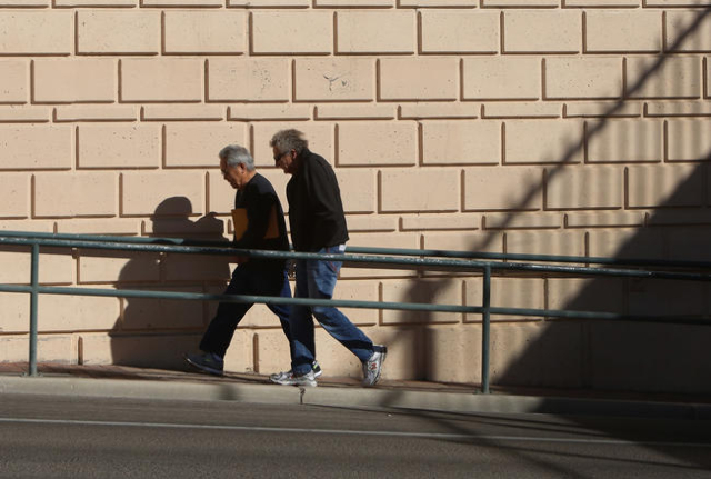 A construction fence casts its shadow on the wall as pedestrians, who did not give thier name, walk on the sidewalk on South City Parkway, near downtown Las Vegas, on Monday, Jan. 25, 2016. (Bizua ...