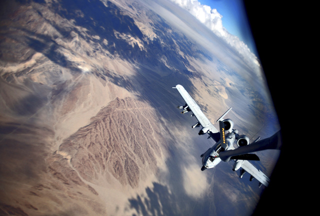 An A-10 Thunderbolt Warthogs, flying at around 18,000 feet, gets fuel from a KC-135T Stratotanker from Michigan's Air National Guard over the Mojave Desert during a Green Flag exercise to su ...
