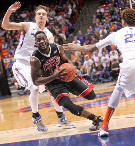 UNLV player Ike Nwamu (34) drives to the basket against defense by Boise State players Anthony Drmic (3) and James Webb III (23) during the game at Taco Bell Arena in Boise, Idaho. Boise State led ...
