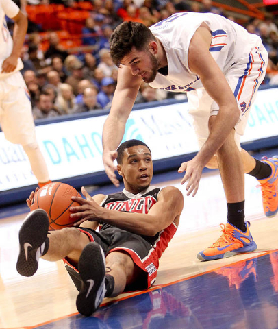 UNLV player Jalen Poyser (24) looks to pass from the floor while being defended by Boise State player Zach Haney (11) during the game at Taco Bell Arena in Boise, Idaho. Boise State led UNLV 35-34 ...