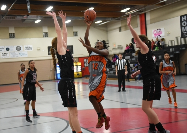 Chaparral's Shanice Aycox (12) shoots the ball against Utah's Layton Christian defenders Lily Henry (10), left, and Kylie Goodwin (24) during the championship game of the Vegas Invitat ...