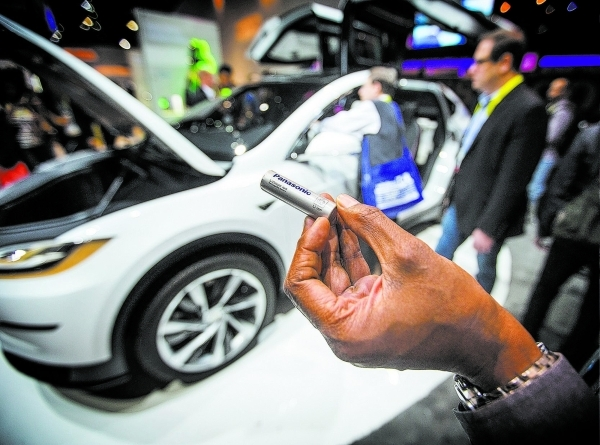 A representative of Panasonic shows a one of the thousands of batteries that will power the Tesla Model X pre-production pro type seen in the background at the Panasonic booth during the Consumer  ...