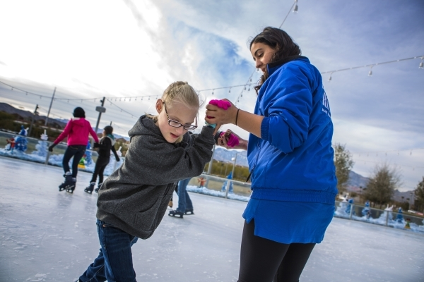 Volunteer Victoria Malkusz, right, holds hands with Kristlynn Allison, 8, who is visually impaired, while teaching her how to skate at  Downtown Summerlin´s Rock Rink on Wednesday, Jan. 13, 201 ...