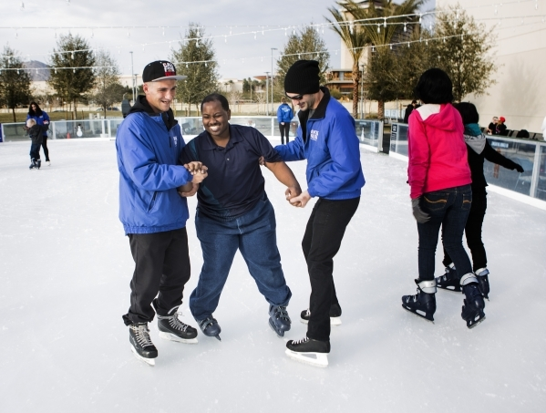 Volunteers Dallis Holmes, left, and John Inzanti, right, assist visually impaired skater Aarius White while skating at  Downtown Summerlin´s Rock Rink on Wednesday, Jan. 13, 2016. Volunteers ga ...