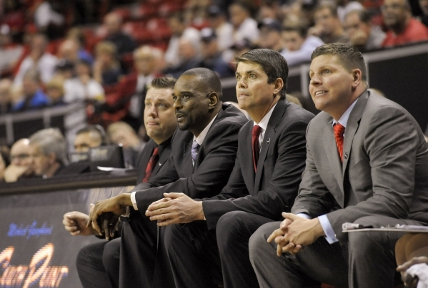 UNLV men's basketball coach Dave Rice, second from right, and his assistants, from left, Todd Simon, Stacey Augmon and Ryan Miller, focus on a play during a Mountain West Men's Basketb ...