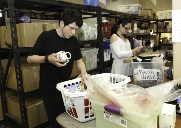 Volunteers Sam Hodgson, left, and Genevieve Dube sort through donated clothing and household items to Project 150 at Brady Caipa Volunteer Center's warehouse on Thursday, Jan. 21, 2016, in L ...