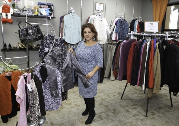 Project 150 Executive Director Meli Pulido displays donated clothing to Project 150 as she poses for a photo at Betty's Boutique on Thursday, Jan. 21, 2016, in Las Vegas. Project 150, the lo ...
