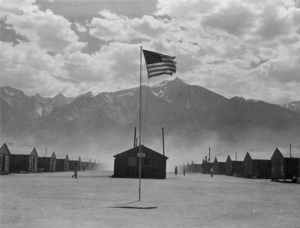 Scene of barrack homes at this War Relocation Authority Center at Manzanar, Calif. for evacuees of Japanese ancestry. A hot windstorm brings dust from the surrounding desert July 3, 1942. Photo by ...