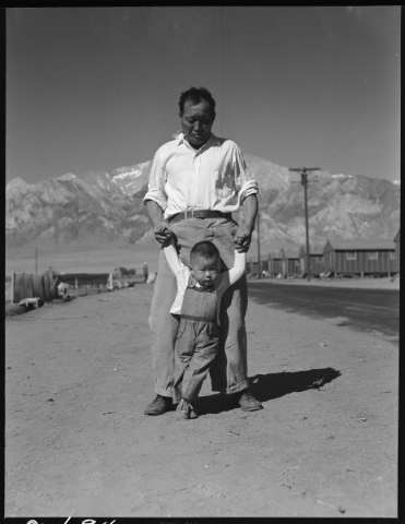 Manzanar Relocation Center, Manzanar, California. Grandfather of Japanese ancestry teaching his grandson to walk at this War Relocation Authority center for evacuees on July 2, 1942. Photo by Doro ...