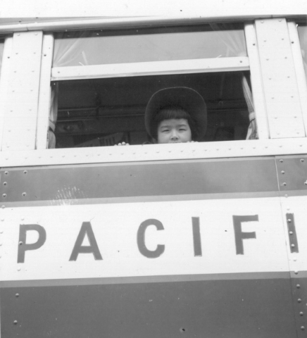 A girl looks out the window of a bus that transported Japanese Americans to wartime assembly centers in this photo taken in May 1942 in Hayward, California. DOROTHEA LANGE/JAPANESE AMERICAN RELOCA ...