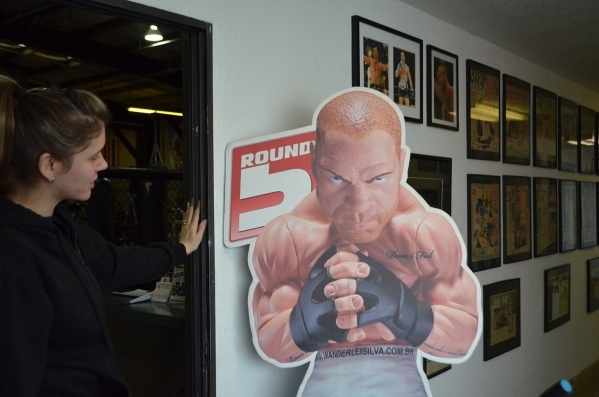 Thaisa Monteiro points out a cardboard cutout of a toy created in honor of Vanderlei Silva, founder of Wand Fight Team Martial Arts & Fitness, 3061 Business Lane. Ginger Meurer/Special to View