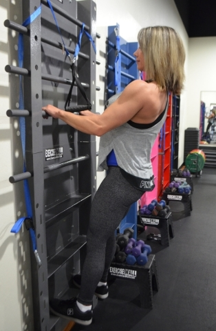Shelly Yakimchuk demonstrates the Excursive Wall, an invention of local trainer Marcus Niemo at YakþÄôs Fitness, 7375 S. Durango Drive.  Ginger Meurer/Special to View
