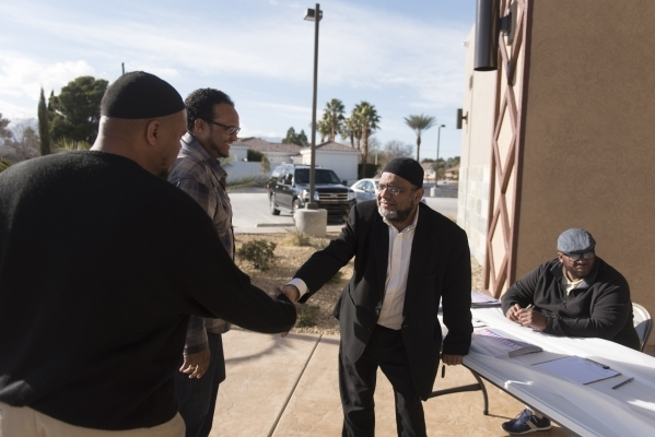 Dr. Aslam Abdullah, center, greets Faruq R. Dowdell, far left, and Kimani Kamau as they arrive for a neighborhood get together during Masjid Ibrahim's opening weekend in Las Vegas Saturday,  ...