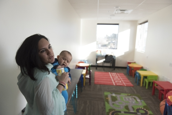 Saira Haseebullah speaks to a reporter as she holds her 10-month-old son Isaac Lee and gives a tour of Masjid Ibrahim during a neighborhood get together for the mosque's opening weekend in L ...