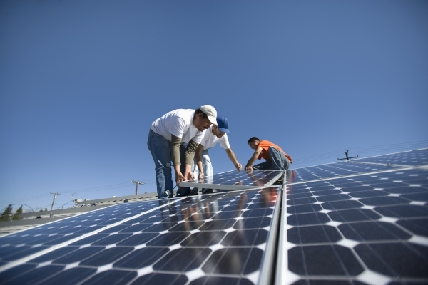 A group of men working on solar panels (Review-Journal File)