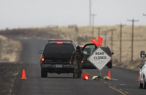 An FBI agent walks by a roadblock near the Malheur National Wildlife Refuge headquarters, where four anti-government protesters remain, about 30 miles south of Burns, Ore., on Friday, Jan. 29, 201 ...
