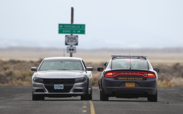 Oregon State Police officers confer near a roadblock near the Malheur National Wildlife Refuge headquarters, where four anti-government protesters remain, about 30 miles south of Burns, Ore., on F ...