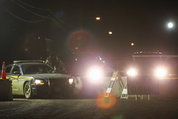 """Law enforcement look on as people participate in a """"rolling"""" protest of the shooting death of LaVoy Finicum, who was killed Tuesday night during an attempted arrest by FBI and Oregon Sta ..."""