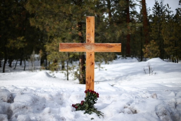 A cross and roses are shown where LaVoy Finicum was shot and killed Tuesday during an attempted arrest by law enforcement about 20 miles north of Burns, Ore. along U.S. Route 395, Friday, Jan. 29, ...