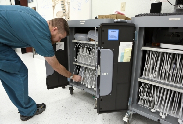 Daniel Bollard, lab manager, looks over a cabinet that holds and charges tablets in a gross anatomy lab at Touro University Nevada Tuesday, Feb. 2, 2016, in Henderson. Students use the tablets to  ...