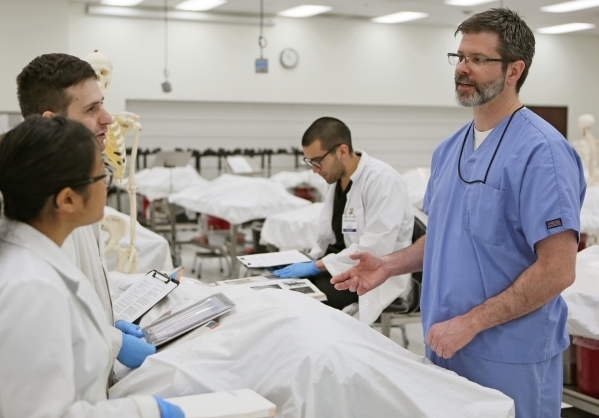 Dr. Emmett Findlay, right, director of anatomy, speaks to first year medical students Diana Trang, far left, and Graydon Taylor, left, during a break in a gross anatomy lab at Touro University Nev ...