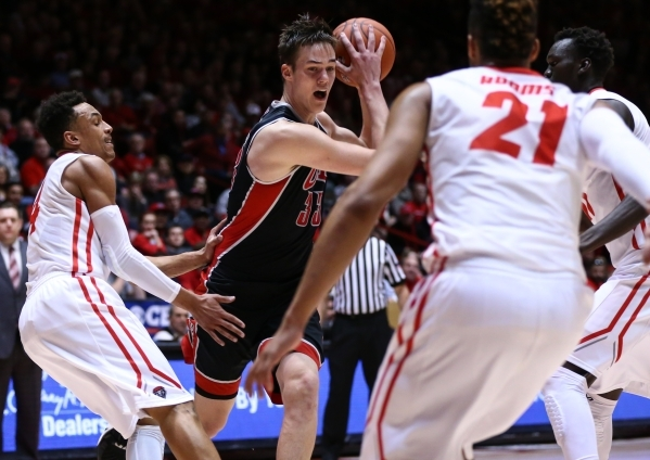 UNLV forward Stephen Zimmerman Jr. (33) drives past New Mexico guards Elijah Brown (4) and Xavier Adams (21) during a basketball game at WisePies Arena in Albuquerque on Tuesday, Feb. 2, 2016. UNL ...