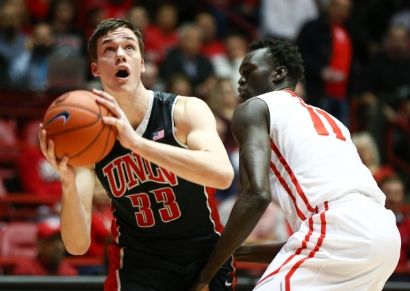 UNLV forward Stephen Zimmerman Jr. (33) looks to shoot over New Mexico center Obij Aget (11) during a basketball game at WisePies Arena in Albuquerque on Tuesday, Feb. 2, 2016. UNLV lost 87-83. Ch ...