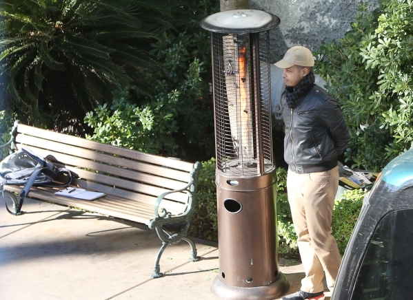 A hotel gust who did not give his name stands near a portable patio heater as he waits for a shuttle bus at the Treasure Island hotel-casino on Tuesday, Feb. 2, 2016, in Las Vegas. Tuesday's ...