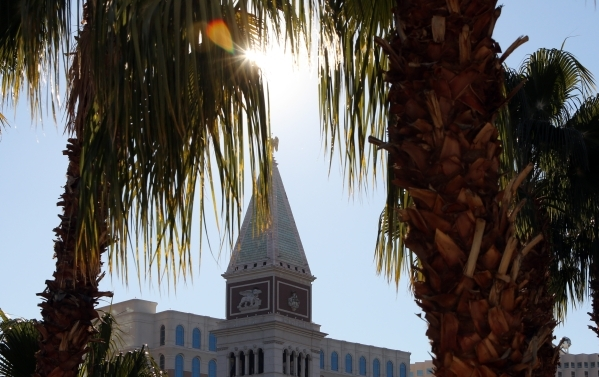 The Venetian hotel-casino is seen as morning sun light rays piercing through palm trees on Tuesday, Feb. 2, 2016, in Las Vegas. Tuesday's expected high is 46 degrees and the low is just belo ...