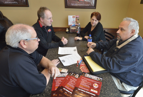 Marco's Pizza franchisee and area representative Tom Billow, left, and Steve Hoza, director of real estate for the company, second from left, talk about franchising opportunities with Nila D ...