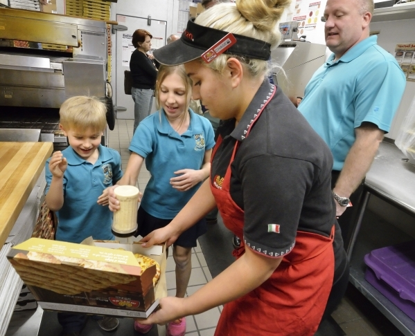 Andrew Stewart, left, watches as his sister Ellie adds cheese to an order for store manager Chase Billow at MarcoþÄôs Pizza at 3400 S. Hualapai Way in Las Vegas on Thursday, Feb. 4, 2016. ...