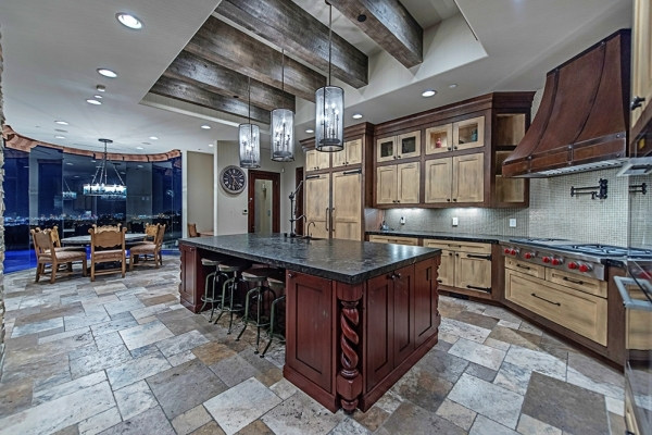 The kitchen is equipped with high-end appliances designed to create culinary masterpieces. The cabinetry is made of a light custom-aged wood framed by darker molding. Dark granite countertops with ...