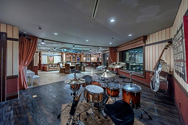 The theater is transformed into a recording studio using soundproof walls and custom-built hidden recording equipment. There is a stage downstairs in the game room where musicians can play while a ...