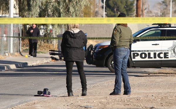 A crime scene photographer prepares to take pictures where Las Vegas police are investigating a homicide at an apartment complex near downtown on 2300 Olive Street, near where Charleston Boulevard ...