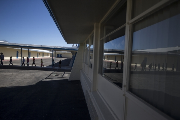 Children walk on school grounds at Lomie Heard Elementary School inside Nellis Air Force Base on Tuesday, Feb. 9, 2016, in Las Vegas. The school will close its doors at the end of the school year  ...