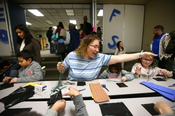 "Sarai Hoopes helps out with the ""parachutes and roto-coptors"" activity during family math and science night at Bendorf Elementary School in Las Vegas on Thursday, Feb. 4, 2016. The schoo ..."