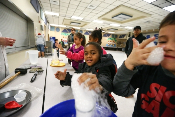 Five-year-old Joshua Spellman, center, and Carlos Murrieta check out bubbling C02 during family math and science night at Bendorf Elementary School in Las Vegas on Thursday, Feb. 4, 2016. The scho ...