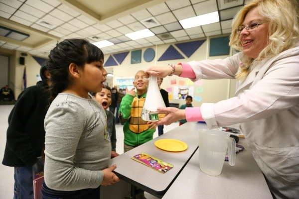 Eight-year-old Valentina Benachi, left, gets a taste of C02 from Kim Sword during family math and science night at Bendorf Elementary School in Las Vegas on Thursday, Feb. 4, 2016. The school is o ...
