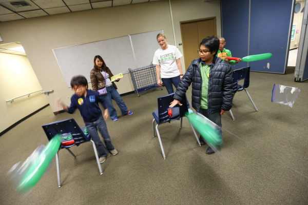 "Eight-year-old Sovann Yem, left, and his brother Serei,  10, compete in the ""balloon rockets"" activity as their mother, Theresia, second from left, looks on with Lindsay Briggs during fa ..."