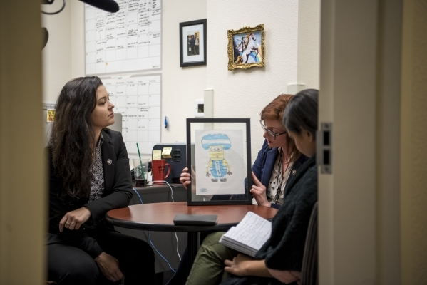 Alissa Cooley, left, and Katelyn Leese show artwork of children they have helped during an interview at the Thomas & Mack Legal Clinic on the campus of UNLV in Las Vegas on Monday, Feb. 8, 201 ...