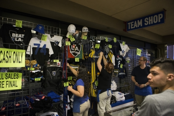 Fans buy team merchandise before the start of the Major League Soccer friendly game between the Los Angeles Galaxy and San Jose Earthquakes at Cashman Field on Saturday, Feb. 13, 2016, in Las Vega ...