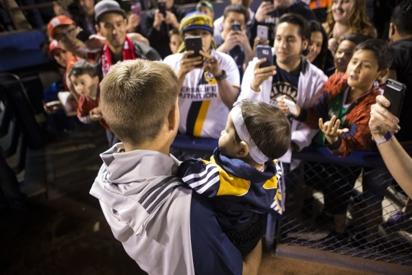 Los Angeles Galaxy's Steven Gerrard (8) poses with a fan's baby after his team's victory 1-0 against San Jose Earthquakes in their Major League Soccer pre-season game at Cashman  ...