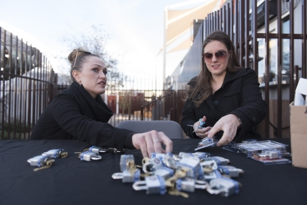 Nova May, artist of the Love Locket sculpture, left, and Angel Sugg of the Downtown Project, prepare locks for sale to be added onto May's sculpture at Downtown Container Park at 707 Fremont ...