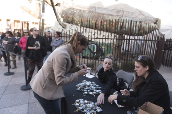Caroline Moriarty of Downtown Container Park, from left, Nova May, artist of the Love Locket sculpture and Angel Sugg of the Downtown Project, prepare locks for sale to be added onto May's s ...