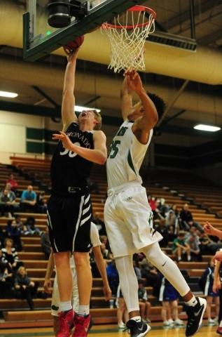 Coronado forward Kennedy Koehler (30) goes up for a shot against Green Valley forward Isiah Macklin (35) in the third quarter of their prep basketball game at Green Valley High School in Henderson ...