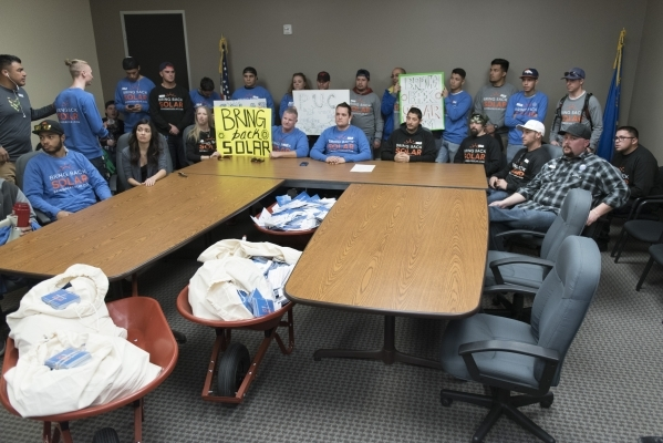 Solar workers and supporters gather inside the overflow room during a hearing bring with them three wheelbarrows filled with approximately 30,000 signatures of people who support restoring old roo ...