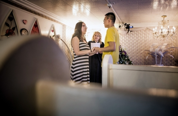Charolette Richards, owner of A Little White Wedding Chapel, 1301 Las Vegas South Boulevard, officiates the wedding of Javelin Yau, left, and Bradon Lee, from Beijing, China, on Monday, Feb. 8, 20 ...