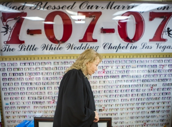 Charolette Richards, owner of A Little White Wedding Chapel, 1301 Las Vegas South Boulevard, stands beside a wall of newlyweds photos who got married on July 7, 2007  while standing in her office  ...