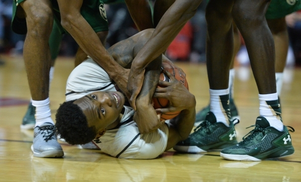 UNLV Rebels forward Dwayne Morgan (15) holds onto the ball while Colorado State Rams players try to steal it during a game against Colorado State at the Thomas & Mack Center in Las Vegas on Sa ...